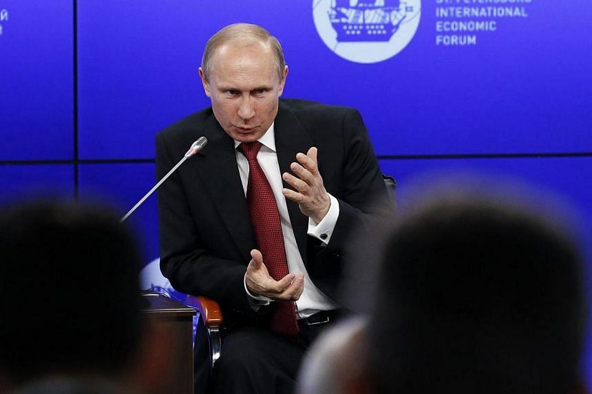Russia's President Vladimir Putin speaks during a session of the St. Petersburg International Economic Forum 2014 in St Petersburg on May 23, 2014. Mr Putin said on Friday that the crisis in Ukraine had evolved into a full-scale civil war, blami