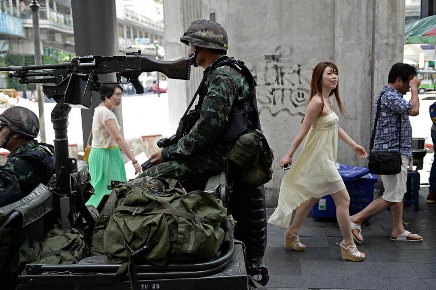 People walk past Thai army soldiers sitting in a jeep mounted with a machine gun as they secure a main intersection in Bangkok on May 20, 2014. The new ruling junta on Friday warned it would block any social media platforms in the country found