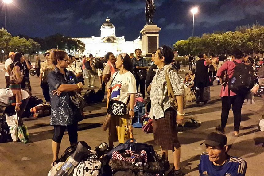 Anti-government protesters waiting on Thursday night at the Royal Plaza in inner Bangkok for buses arranged by the military to send them back home to various provinces. - PHOTO:TAN HUI YEE