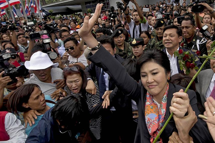 Ousted Thai Prime Minister Yingluck Shinawatra waves to her supporters in a suburb of Bangkok on May 7, 2014. -- PHOTO: AFP