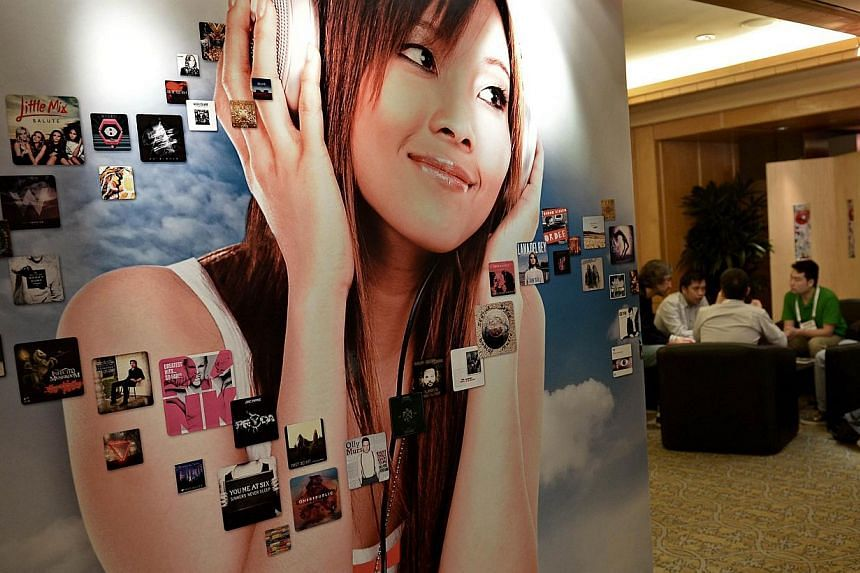 People sit at a booth during the Music Matters conference in Singapore on May 22, 2014. Music Matters, an annual music conference and live music festival, returns with a line-up of more than 60 bands from 18 places performing over four days.--