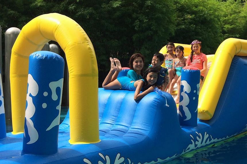 Friends at Ian Lee's birthday bash played on a water float while their parents kept an eye on them. --PHOTO: BOUNCY CASTLES