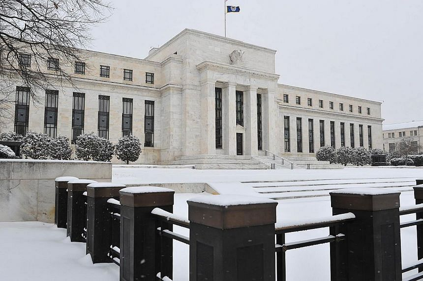 """The US Federal Reserve is seen during a snow storm in in Washington, DC on March 3, 2014. After years of pulling out the stops to boost a stubbornly sluggish US economy, the Federal Reserve is moving back to """"normal"""" monetary policy, a top Fed offici"""