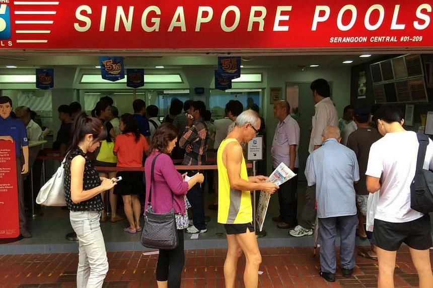 People queue at a Singapore Pools outlet at Serangoon Central Drive on Friday, May 23, 2014.Four people are holding the winning tickets for Friday's Toto $5 million anniversary draw. -- ST PHOTO: KEVIN LIM
