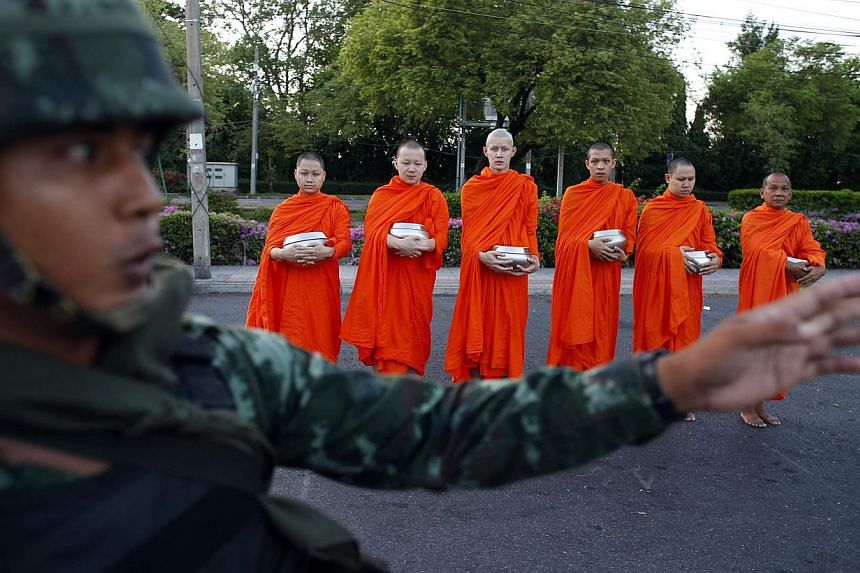 A Thai soldier stands guard while Buddhist monks beg for alms outside a temple near Government House in Bangkok on May 23, 2014. -- PHOTO: REUTERS