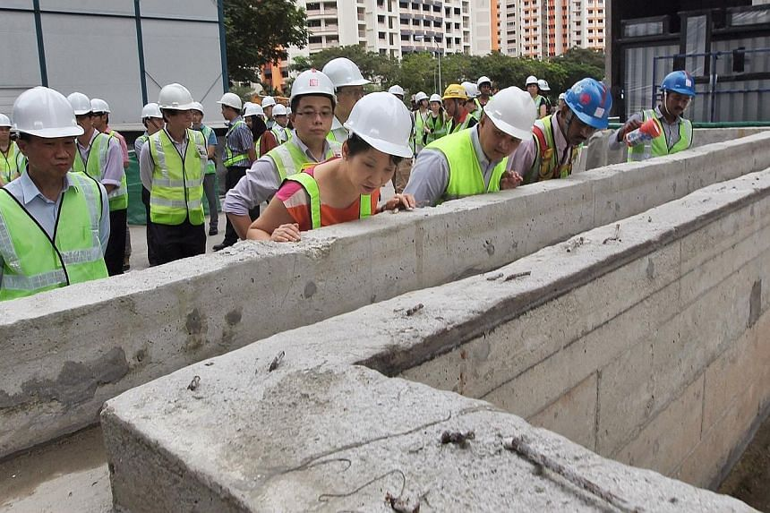 Second Minister for the Environment and Water Resources Grace Fu (in orange) checks out a possible stagnant water area at the future swimming pool of The Luxurie at Compassvale (Sengkang) construction site. She was there to observe the housekeeping r
