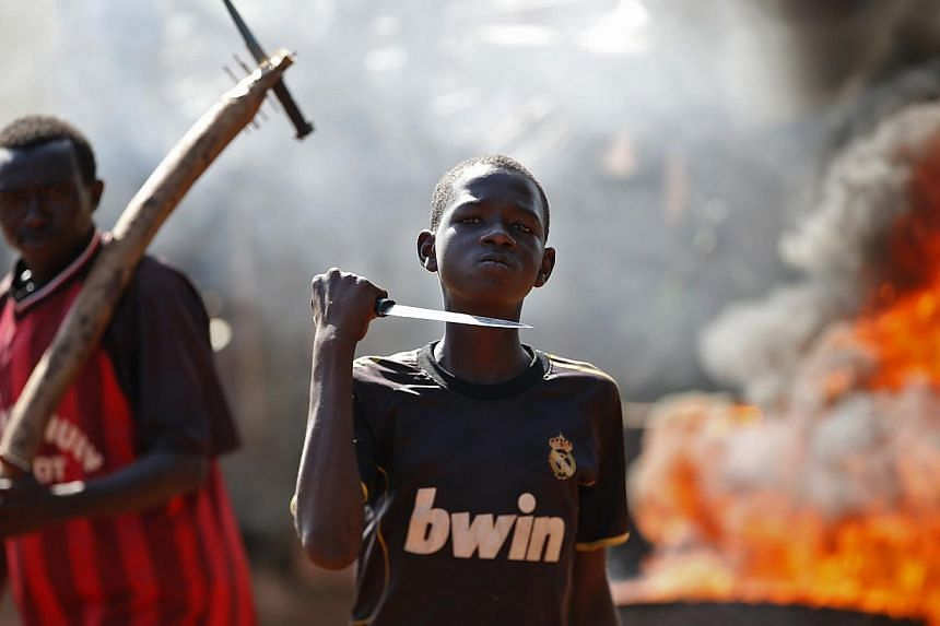 A boy gestures in front of a barricade on fire during a protest after French troops opened fire at protesters blocking a road in Bambari on May 22, 2014. -- PHOTO: REUTERS