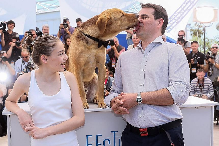 (From left) Actress Zsofia Psotta, Hagen the dog, and White God director Kornel Mundruczo posing for photographers at the Cannes Film Festival on May 17, 2014. -- PHOTO: EPA