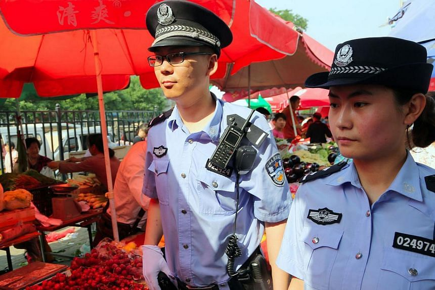 Armed policemen patrol a market, after attackers ploughed two vehicles into a market and threw explosives, killing at least 31 people, in Urumqi in northwest China's Xinjiang region, in Beijing on May 23, 2014. -- PHOTO: AFP