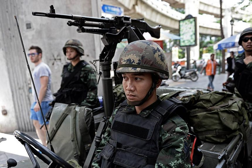 Thai army soldiers sit in a jeep mounted with a machine gun as they secure a main intersection in Bangkok on May 20, 2014. -- PHOTO: AFP