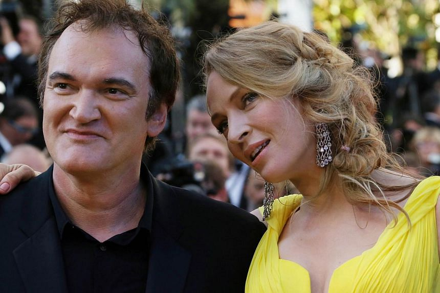"""US actress Uma Thurman (right) and US director Quentin Tarantino pose as they arrive for the screening of the film """"Sils Maria"""" at the 67th edition of the Cannes Film Festival in Cannes, southern France, on May 23, 2014."""
