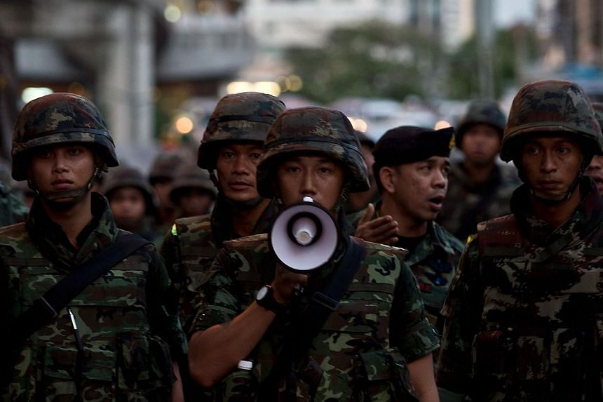 Thai army soldiers urge anti-coup protestors to maintain law and order during a protest in downtown Bangkok on May 23, 2014. -- PHOTO: AFP