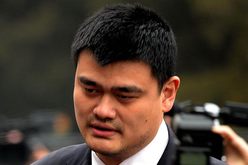 Former NBA star Yao Ming gets mobbed by the media as he arrives for the opening session of the Chinese People's Political Consultative Conference (CPPCC) at the Great Hall of the People in Beijing on March 3, 2014. -- PHOTO: AFP