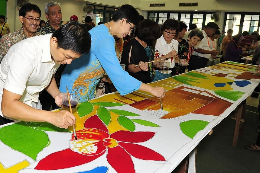 Minister for Manpower Tan Chuan-Jin and MP for Marine Parade GRC Fatimah Lateef have a go at painting batik prints.-- PHOTO:DIOS VINCOY JR FOR THE STRAITS TIMES