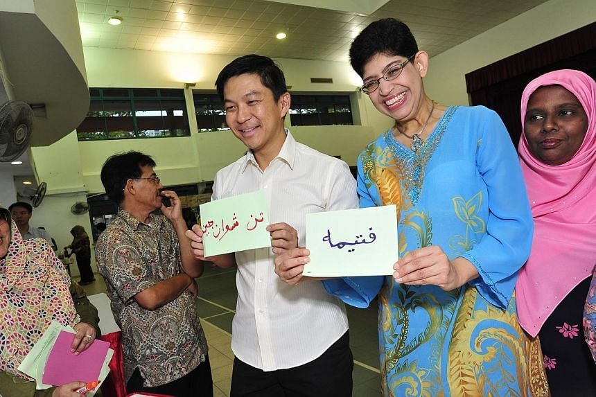 Minister for Manpower Tan Chuan-Jin and MP for Marine Parade GRC Fatimah Lateef show off their names written in Jawi calligraphy.-- PHOTO:DIOS VINCOY JR FOR THE STRAITS TIMES