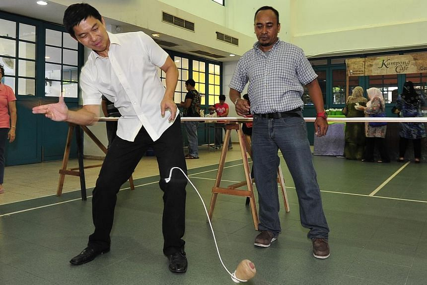 Minister for Manpower Tan Chuan-Jin tries out gasing, a traditional Malay game involving a spinning wooden top.-- PHOTO:DIOS VINCOY JR FOR THE STRAITS TIMES