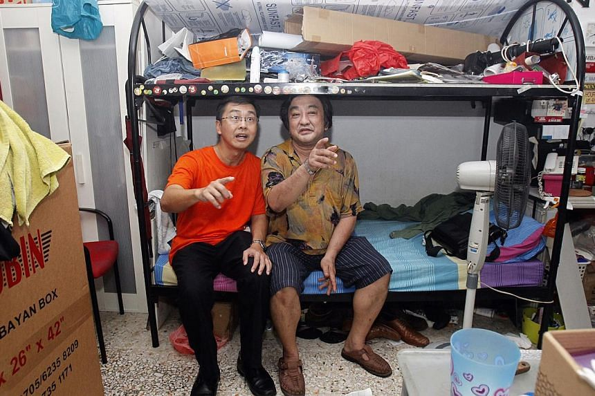 National Council of Social Service chief Sim Gim Guan (left) chatting with a resident while distributing hampers to low-income families last week. The statutory board will have a central system to recruit and train social service leaders.
