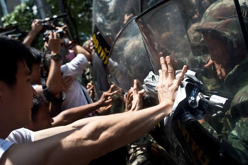 Anti-coup protesters scuffle with Thai soldiers ahead of a planned gathering in Bangkok on May 24, 2014. - PHOTO: AFP