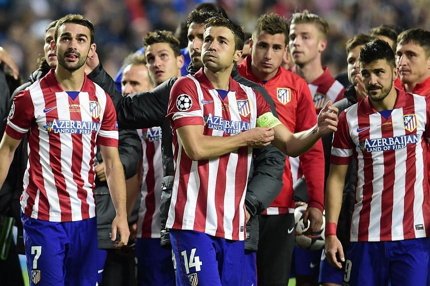 (From left) Atletico Madrid's forward Adrian Lopez, Atletico Madrid's midfielder and captain Gabi and Atletico Madrid's forward David Villa react at the end of the Uefa Champions League Final Real Madrid vs Atletico de Madrid at Luz stadium in Lisbon