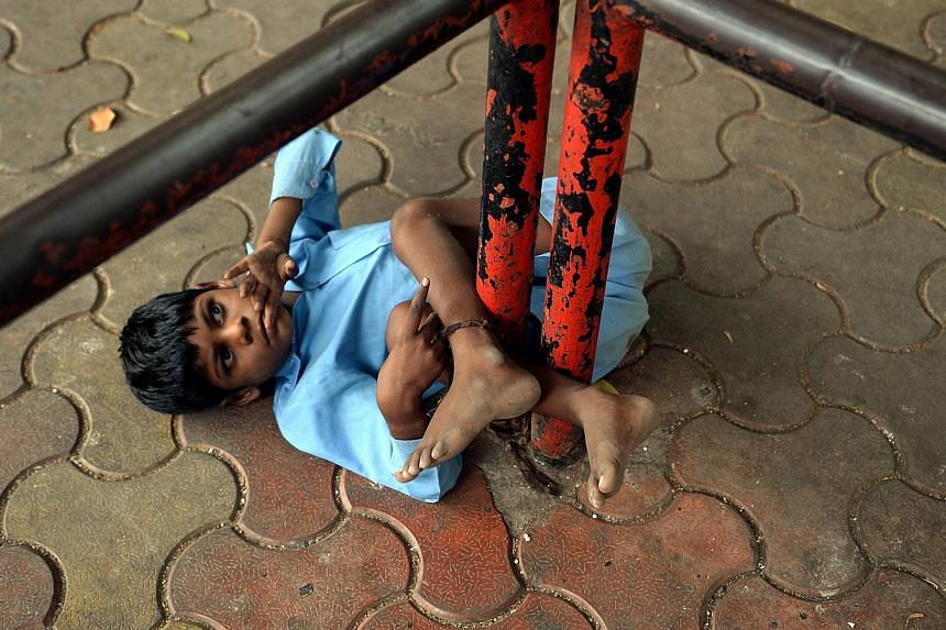 In this photograph taken on May 20, 2014 nine year old Indian boy Lakhan Kale is tied with a cloth rope around his ankle, to a bus-stop pole in Mumbai. Lakhan Kale cannot hear or speak and suffers from cerebral palsy and epilepsy, so his grandmother