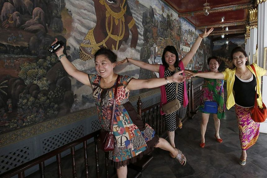 Chinese tourists pose for a picture inside the Grand Palace in Bangkok on May 24, 2014. -- PHOTO: REUTERS