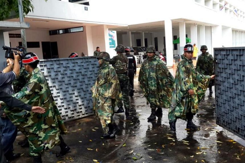 Soldiers closing the gates of the army office on Sunday morning after prominent Thai journalist Pravit Rojanaphruk walked in to report to the junta.Mr Pravit is the first journalist to be summoned by the junta since it seized power on Thursday. -- ST