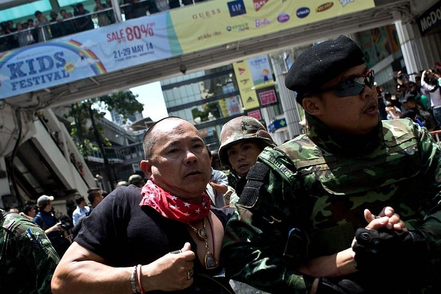 Thai soldiers take away an alleged Red-Shirt protester ahead of a planned gathering in Bangkok on May 25, 2014. Thailand's military junta said it had disbanded the Senate and placed all law-making authority in the hands of the army chief, dramaticall