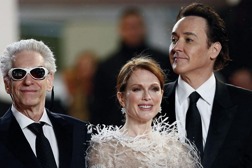 (left-right) Canadian director David Cronenberg, US actress Julianne Moore and US actor John Cusack arrive for the screening of Maps To The Stars during the 67th annual Cannes Film Festival, in Cannes, France, May 19, 2014. Julianne Moore won th