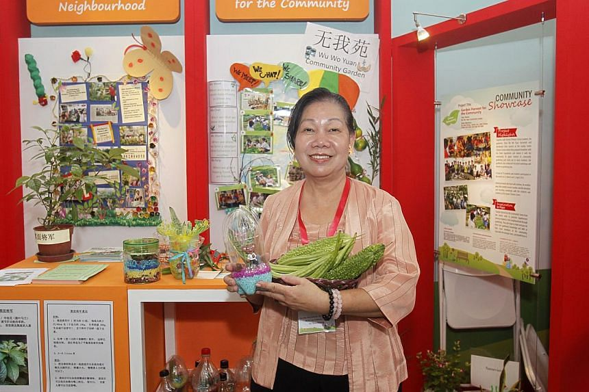 Madam Iris Chua, a 61-year-old retiree, with her neighbourhood-grown bittergourds and ladyfingers as part of a showcase of Good Neighbours Projects which promote neighbourliness in Singapore, at Toa Payoh HDB Hub Atrium on May 24, 2014. -- ST PHOTO: