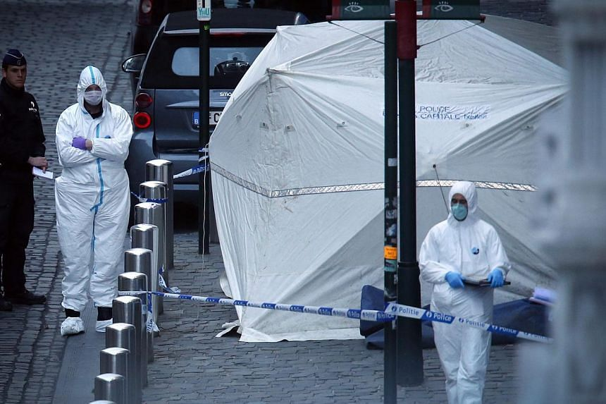 Police officers and crime scene investigators work in the cordoned off area of shooting near the Jewish Museum in Brussels, Belgium, on May 24, 2014. - PHOTO: EPA
