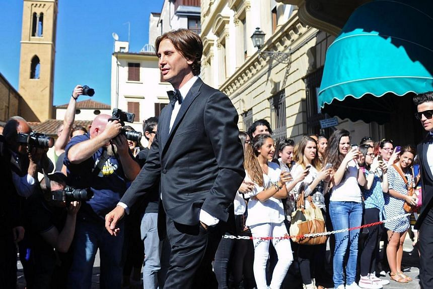 Jonathan Cheban (centre) walks out of the hotel for the wedding of Kim Kardashian and Kanye West in Florence, Italy, on May 24, 2014. -- PHOTO: EPA