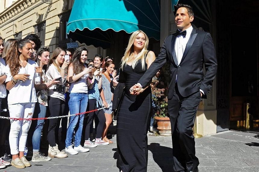 US entrepreneur Joe Francis and his girlfriend Abbey Wilson walk out of the hotel for the wedding of Kim Kardashian and Kanye West in Florence, Italy, on May 24, 2014. -- PHOTO: EPA