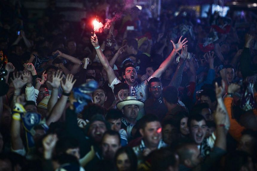 Real Madrid supporters light flares after a team goal in Lisbon on May 24, 2014 during the UEFA Champions League final football match Real Madrid CF vs Club Atletico de Madrid. - PHOTO: AFP