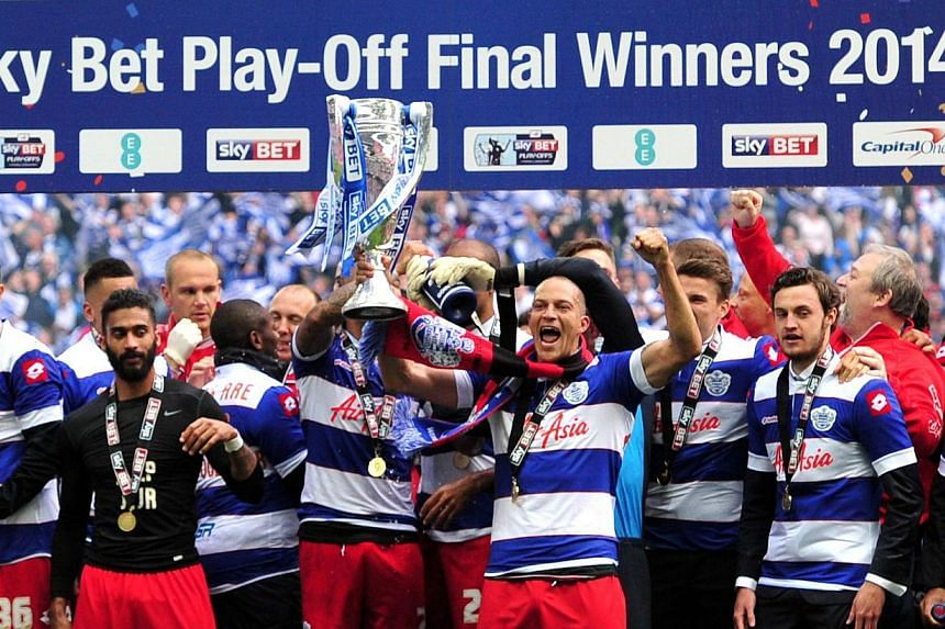 Queens Park Rangers (QPR) players celebrate with the trophy after winning the English Championship Play Off final football match against Derby County at Wembley Stadium in London on May 24, 2014. -- PHOTO: AFP