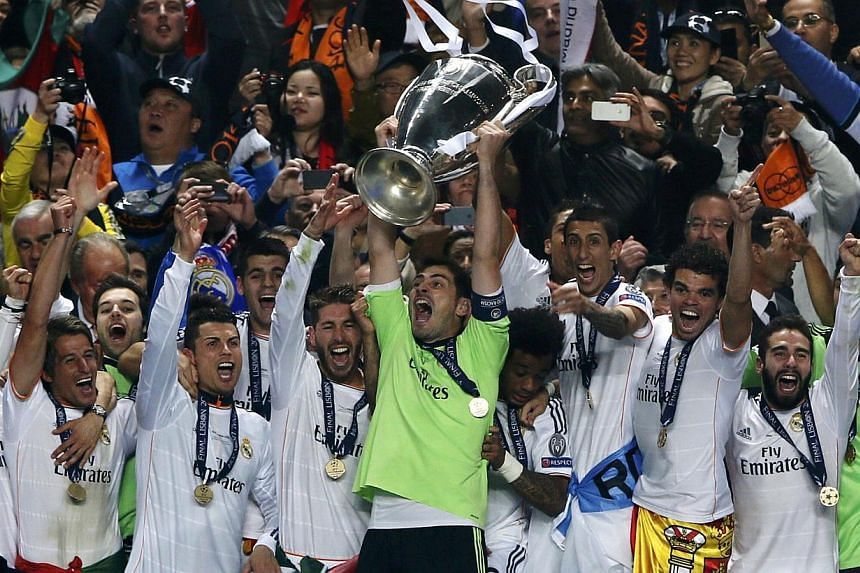 Real Madrid's captain Iker Casillas and team mates celebrate with the trophy after defeating Atletico Madrid in the their Champions League final match at the Luz Stadium in Lisbon, on May 24, 2014. - PHOTO: REUTERS