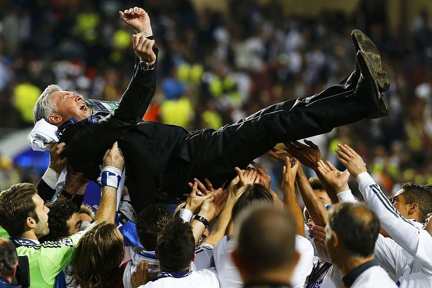 Real Madrid's coach Carlo Ancelotti is thrown in the air by his team after defeating Atletico Madrid in their Champions League final match at Luz stadium in Lisbon, on May 24, 2014. - PHOTO: REUTERS.