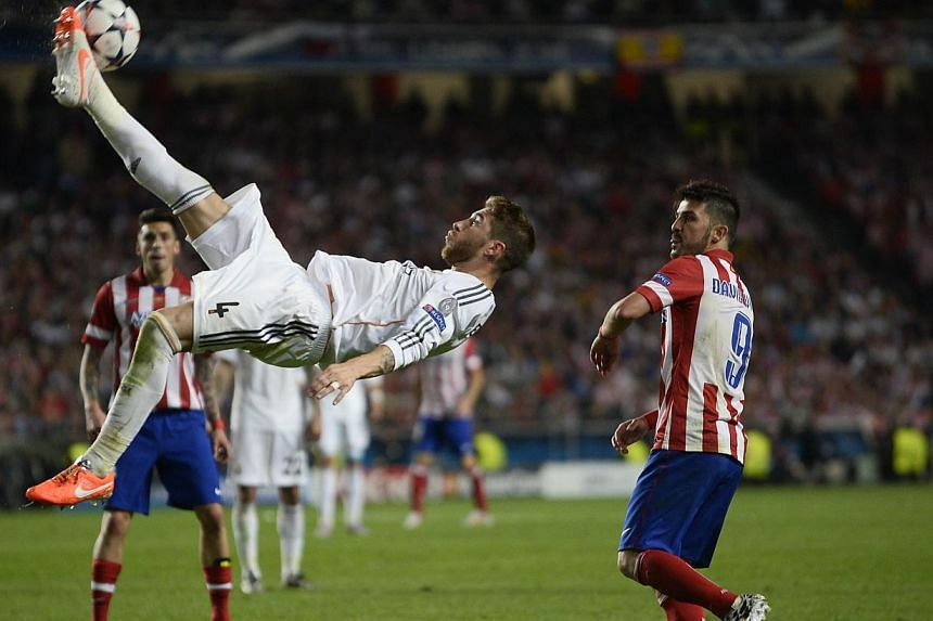 Real Madrid's defender Sergio Ramos (left) jumps to kick the ball during the UEFA Champions League Final against Atletico Madrid at Luz stadium in Lisbon, on May 24, 2014. - PHOTO: AFP