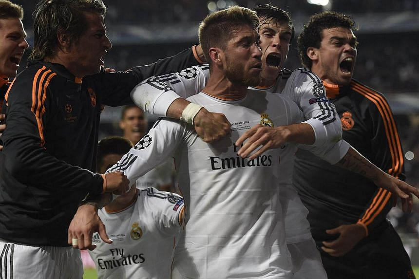 Real Madrid's defender Sergio Ramos (centre) is congratulated by teammates after scoring during the UEFA Champions League Final against Atletico Madrid at Luz stadium in Lisbon, on May 24, 2014. - PHOTO: AFP