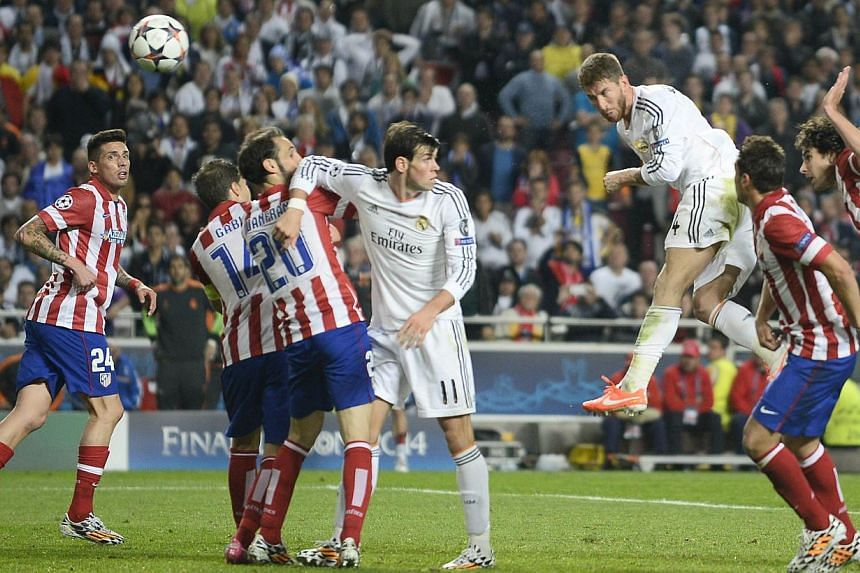 Real Madrid's defender Sergio Ramos (third, right) scores during the UEFA Champions League Final Real Madrid vs Atletico de Madrid at Luz stadium in Lisbon, on May 24, 2014.- PHOTO: AFP