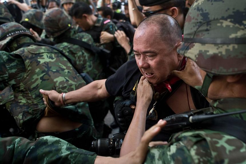 Thai army soldiers take away an alleged Red-Shirt protester ahead of a planned gathering in Bangkok on May 24, 2014. - PHOTO: AFP