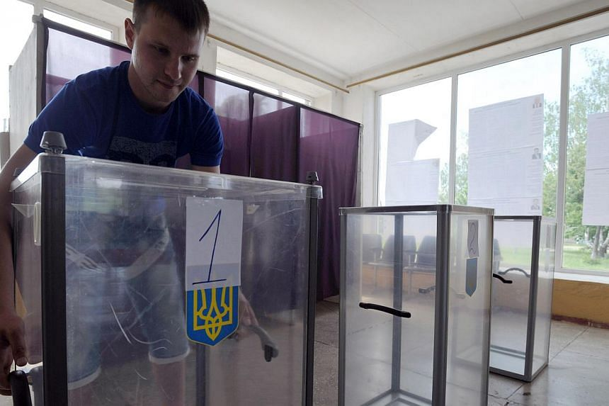A member of the election commission prepares voting boxes at a polling station in a small village bordering the Kharkiv and Donetsk regions on May 24, 2014, a day before early presidential election in the country. - PHOTO: AFP