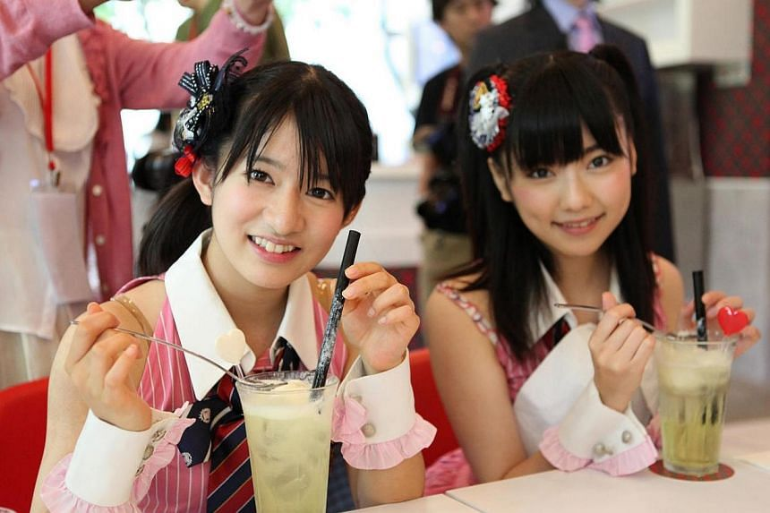 (From left) Miyu Takeuchi and Haruka Shimazaki enjoying items on the menu at the new AKB48 cafe. -- PHOTO: ASIA PR WERKZ
