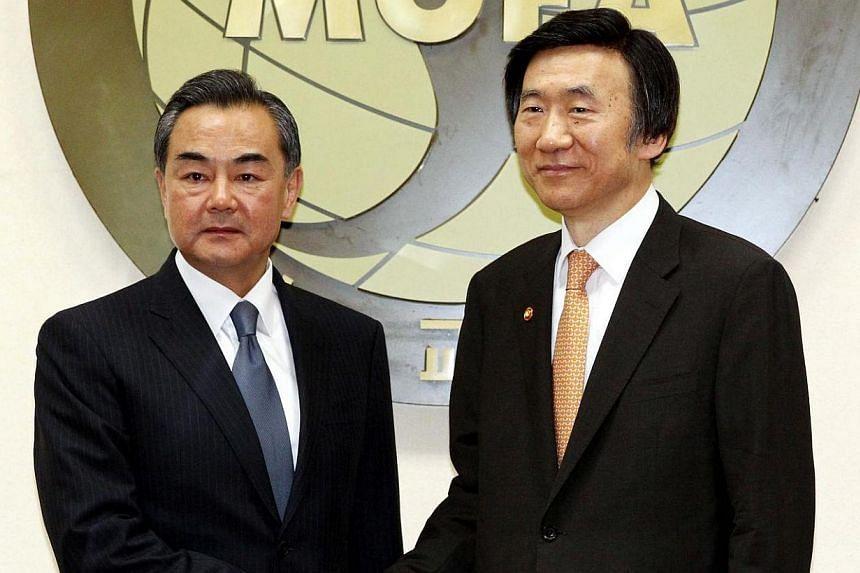 South Korean Foreign Minister Yun Byung Se (right) shakes hands with his Chinese counterpart Wang Yi at the foreign ministry in Seoul, South Korea on May 26, 2014. South Korea and China agreed on Monday, May 26, 2014, recent nuclear activity by