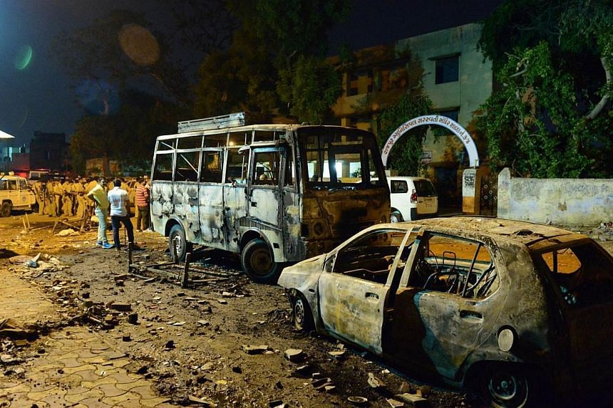 Indian police secure the site of clashes between two groups during which shops and vechiles were set alight in the Gomptipur area of Ahmedabad on late May 25, 2014. -- PHOTO: AFP