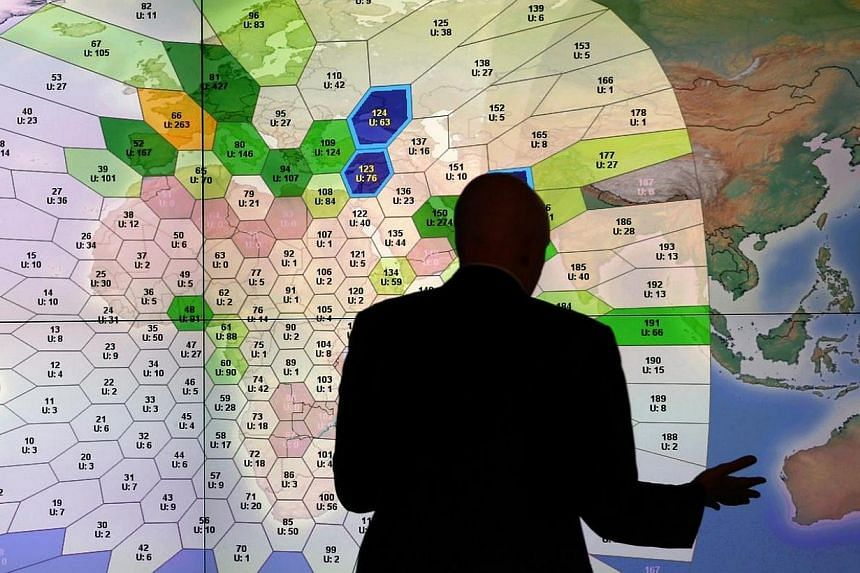 A member of staff at satellite communications company Inmarsat works in front of a screen showing subscribers using their service throughout the world, at their headquarters in London on March 25, 2014.  Major airlines want real-time tracki