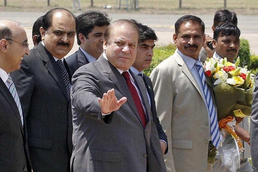 Pakistan's Prime Minister Nawaz Sharif waves upon his arrival at the airport in New Delhi on May 26, 2014.Pakistan Prime Minister Nawaz Sharif arrived in New Delhi on Monday, May 26, 2014, for the swearing-in ceremony of his incoming Indian cou