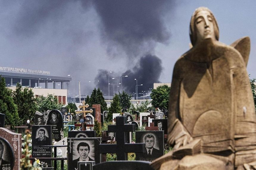Black smoke billows from Donetsk international airport, seen behind a cemetery, during heavy gun battle between the Ukrainian army and pro-Russian militants in the eastern Ukrainian city of Donetsk on May 26, 2014. A fierce battle erupted on Mon