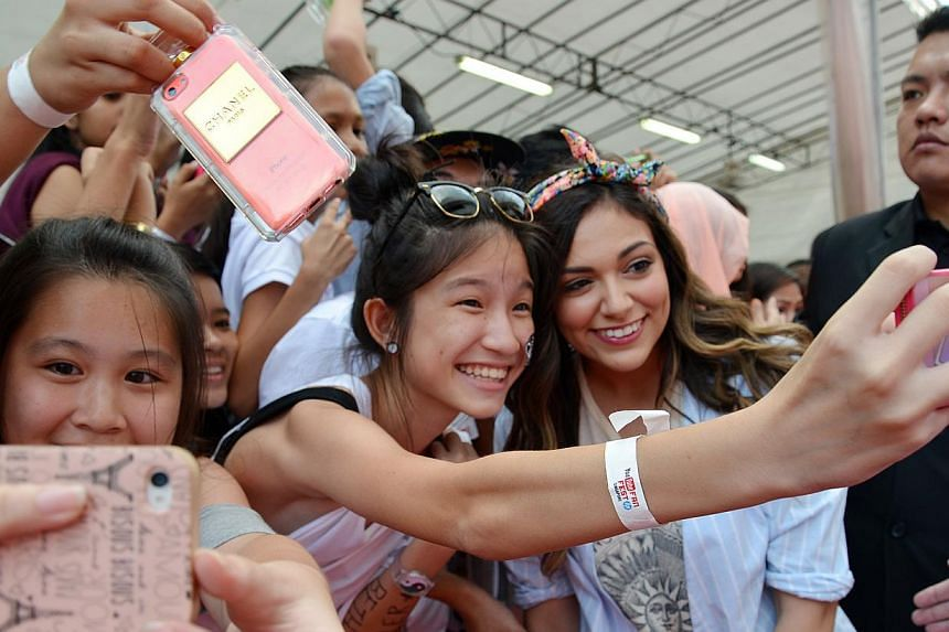 YouTuber Bethany Mota (with ribbon hairband) posing with a fan at the YouTube Fanfest 2014. -- ST PHOTO: BENSON ANG