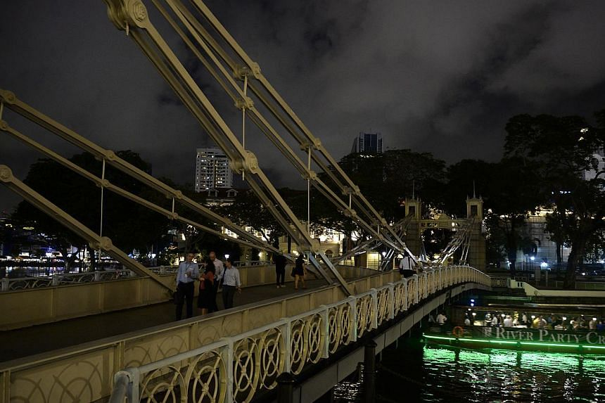 The lights at Cavenagh Bridge (left) no longer work, leaving it shrouded in darkness at night, while peeling paint is visible on the parapet of Read Bridge (right) along the Singapore River.