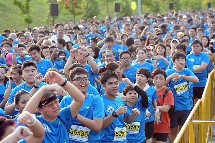 Runners warming up before the 5km fun run at the Straits Times Run in the Park at Punggol Waterway last year. This year's ST Run at the Hub will allow participants to be the first to finish at the new National Stadium.
